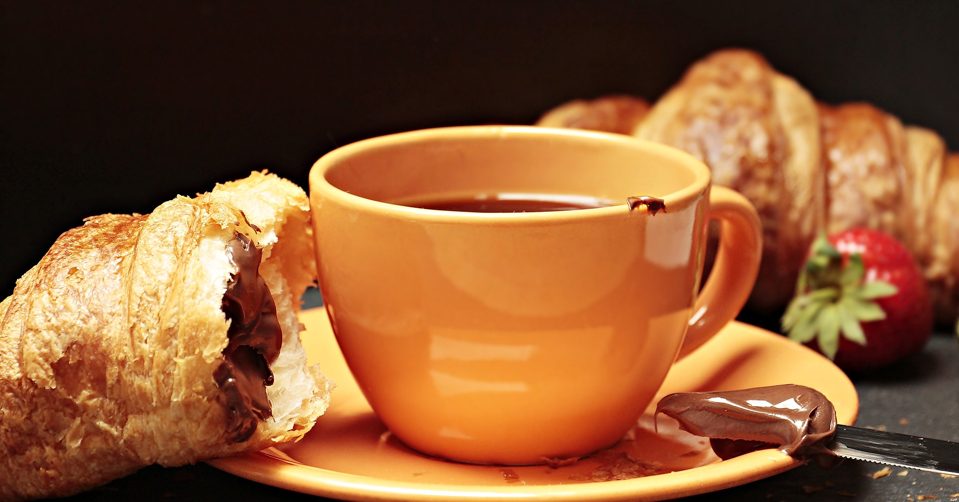 Chocolate croissant on plate with mug of coffee