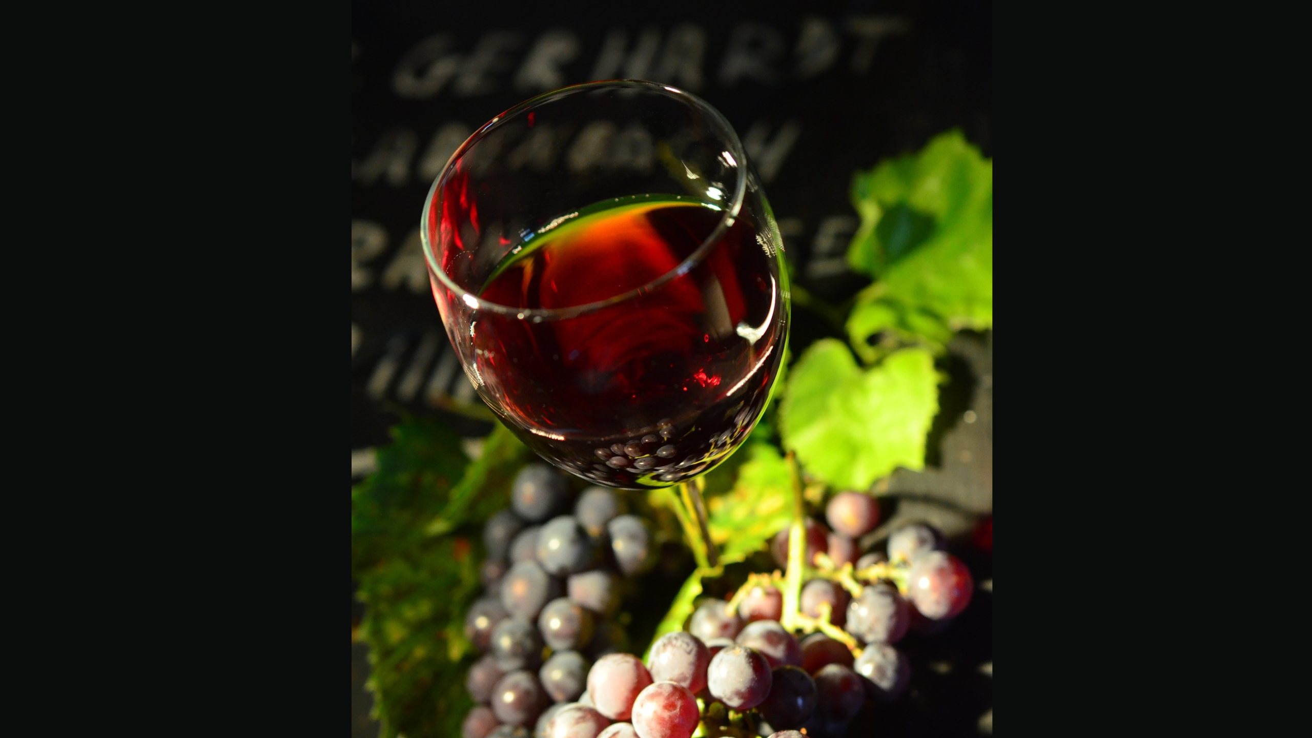 glass of red wine sitting in bunch of red grapes