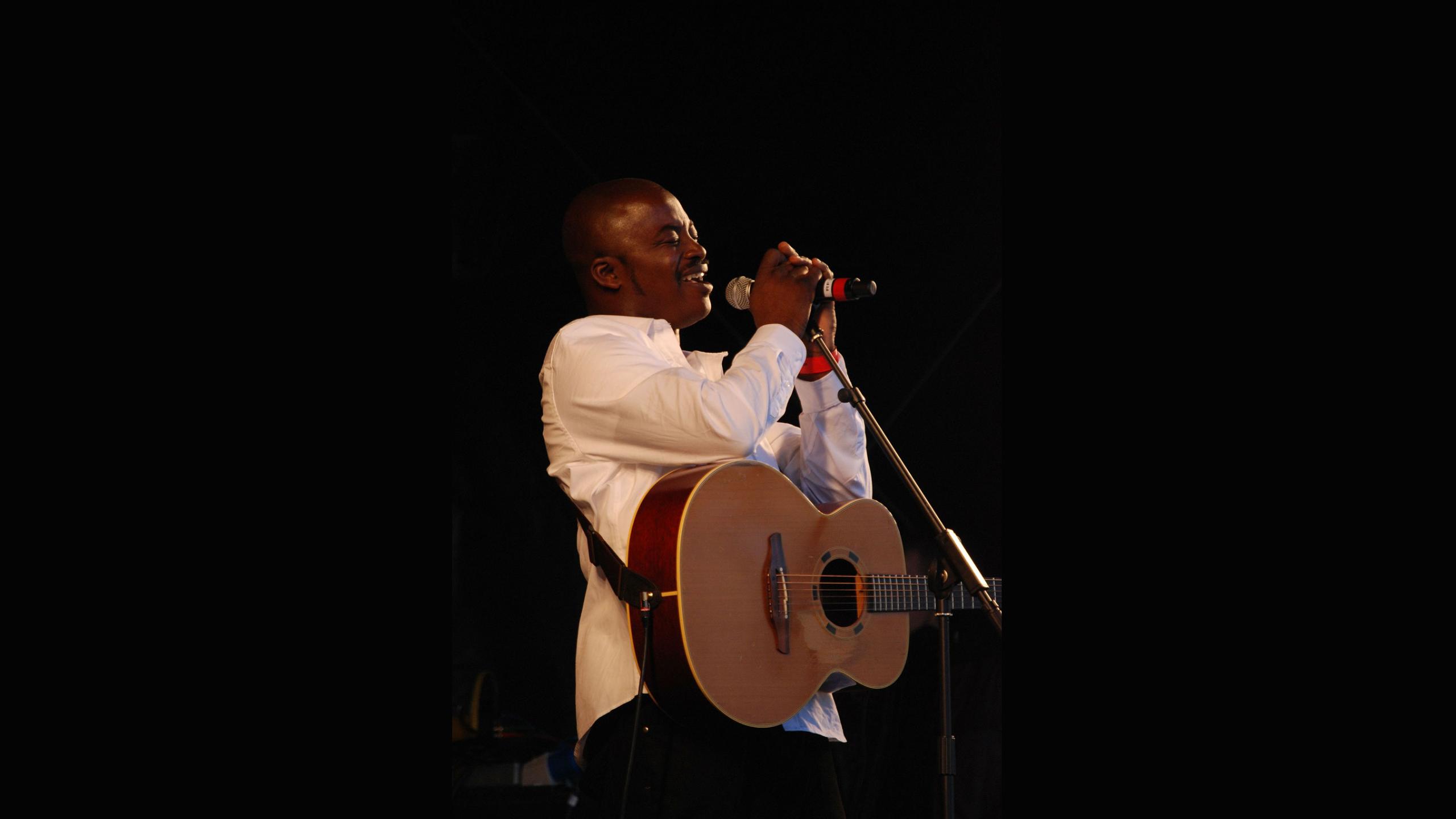 Man singing into microphone advertising Open Mic